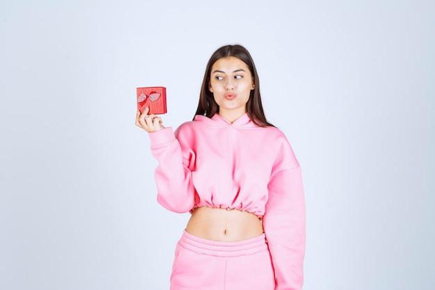 Fille en pyjama rose tenant une petite boîte cadeau rouge.