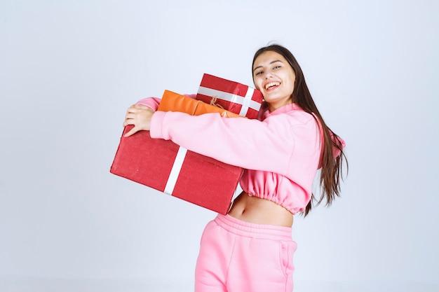 Fille en pyjama rose tenant plusieurs coffrets cadeaux rouges et se sentir heureux.