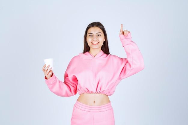 Fille en pyjama rose tenant une tasse de café et montrant quelque chose