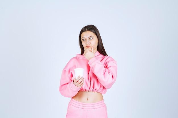 Fille en pyjama rose tenant une tasse de café et de la pensée