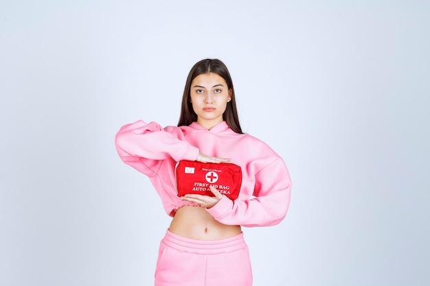 Fille en pyjama rose tenant une trousse de premiers soins rouge et en faisant la promotion.