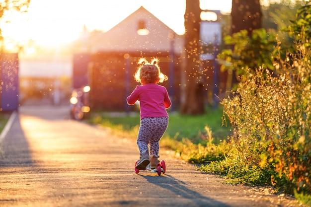 La fille que l'enfant monte dans le parc avec sa mère le scooter