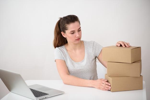 Fille avec des queues de cheval, un t-shirt gris est assis devant un ordinateur portable et regarde une pile de boîtes en carton. service de livraison en ligne