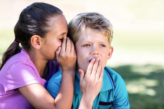 Fille qui chuchote à l'oreille de son frère