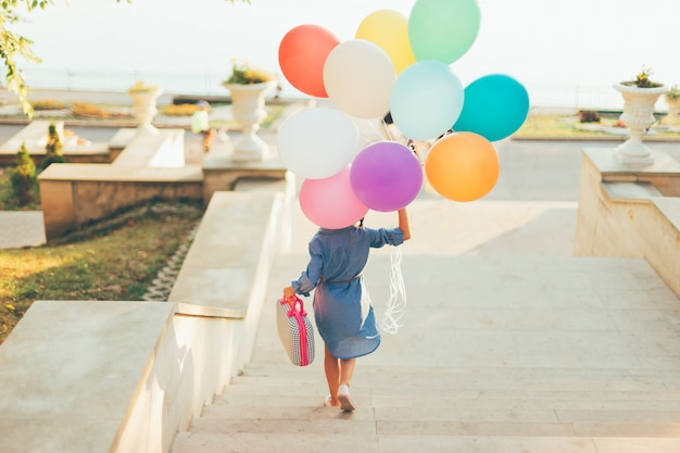 Fille qui court dans les escaliers tenant des ballons colorés et une valise enfantine