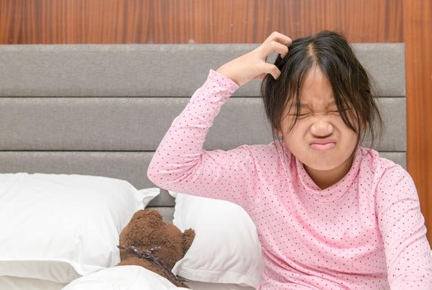 Fille qui démange ses cheveux ou frustré sur le lit, problème de santé concept de cheveux