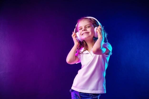 Fille qui écoute de la musique dans les écouteurs sur foncé coloré. danseuse. bonne petite fille danser sur la musique. enfant mignon, appréciant la musique de danse joyeuse.