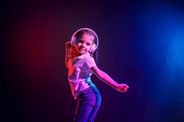 Fille qui écoute de la musique dans les écouteurs sur foncé coloré. néon. danseuse. bonne petite fille danser sur la musique. enfant mignon, appréciant la musique de danse joyeuse.