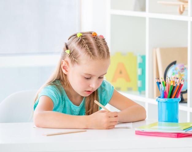 Fille qui écrit avec un crayon