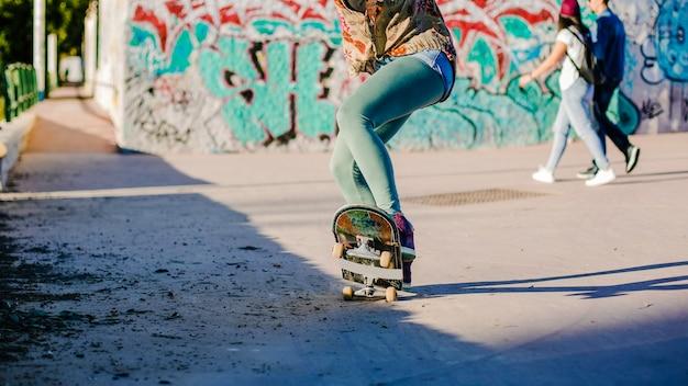 Fille qui fait du skateboard faisant des cascades