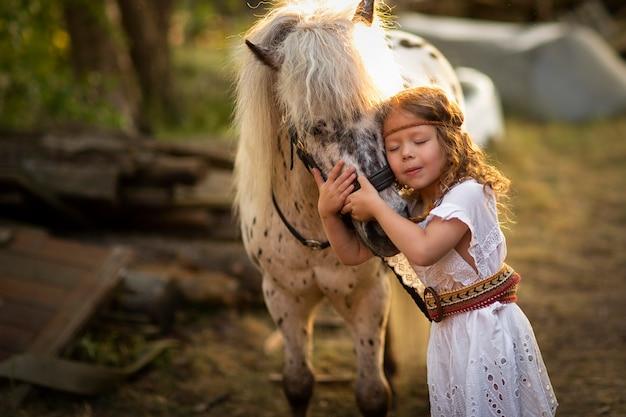 Fille qui marche au coucher du soleil dans un champ avec un cheval