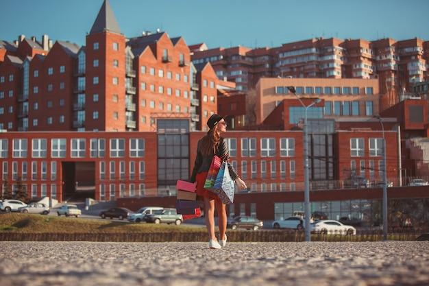 La fille qui marche avec du shopping dans les rues de la ville