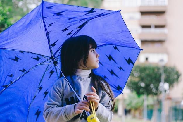 Fille qui marche avec un parapluie