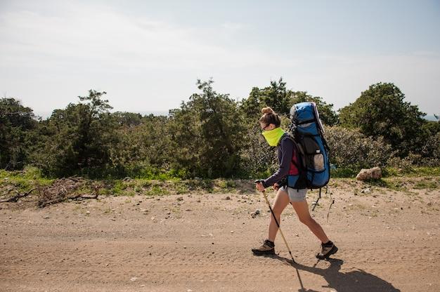 Fille qui marche avec un sac à dos de randonnée et colle un masque spécial contre la poussière