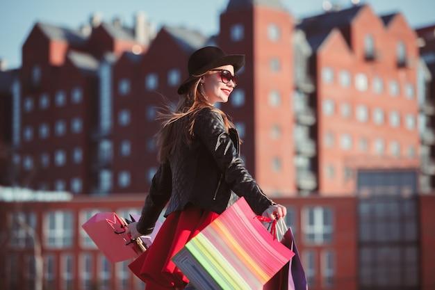 La fille qui marche avec des sacs à provisions dans les rues de la ville à la journée ensoleillée