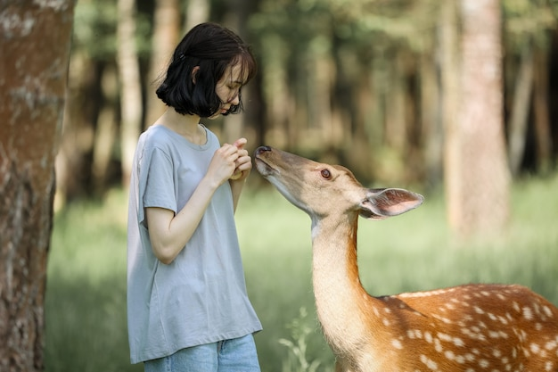 Une fille qui nourrit un mignon bambi de cerf tacheté au zoo pour enfants. happy traveler girl aime socialiser avec les animaux sauvages dans le parc national en été. cerf fauve bébé jouant avec des personnes dans un zoo de contact