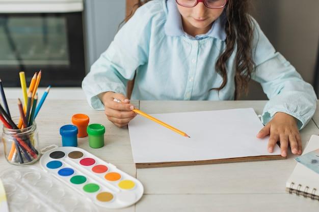 Fille qui peint à l'aquarelle à la maison