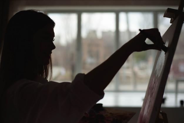 Fille qui peint devant la fenêtre