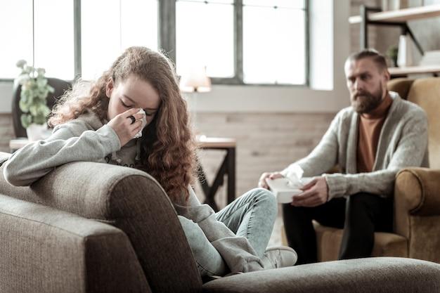 Fille Qui Pleure. Adolescente Bouclée Pleurant En Parlant De Problèmes Familiaux à Un Thérapeute Professionnel Photo Premium