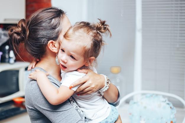 Fille qui pleure sur les mains de la mère à la maison