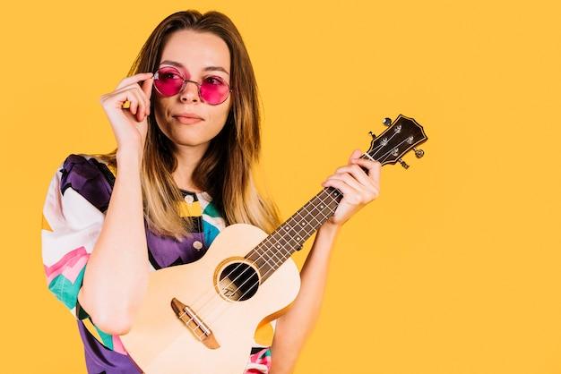 Fille qui porte des lunettes avec un ukelele