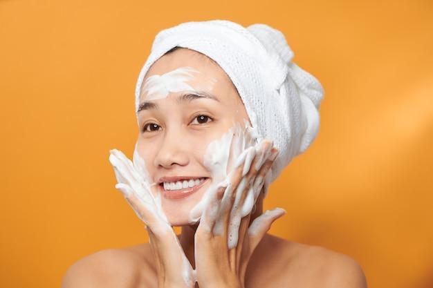 Fille qui rit en appliquant une crème hydratante sur son visage. photo de jeune fille à la peau impeccable sur fond orange. concept de soins de la peau et de beauté