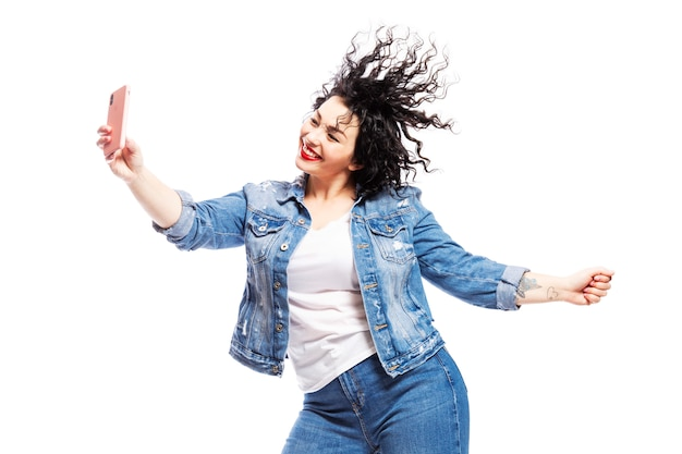 Une fille qui rit et danse regarde le téléphone et prend un selfie