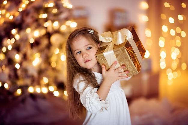 Fille de race blanche avec cadeau de noël cheveux longs, lumières dorées, bokhe