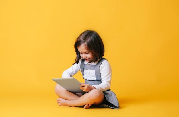 Une fille de race blanche dans une robe grise et une chemise blanche utilise et joue avec une tablette
