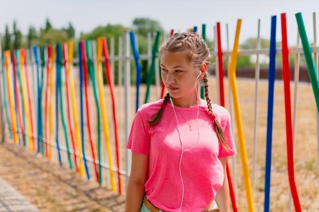 Fille de race blanche dans un t-shirt rose et un casque blanc écoute de la musique. une étudiante sourit, exposant son visage aux rayons du soleil.