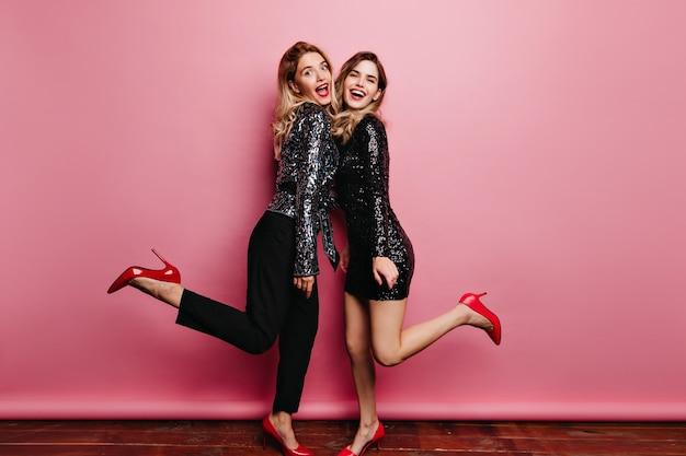 Fille de race blanche galbée dans des chaussures élégantes dansant avec un ami. photo intérieure de soeurs blanches extatiques posant sur un mur rose.