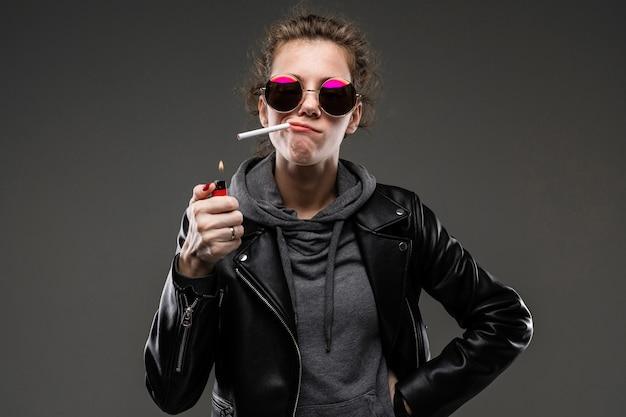 Fille de race blanche avec des traits du visage rugueux dans une veste noire allume une cigarette isolée sur mur noir