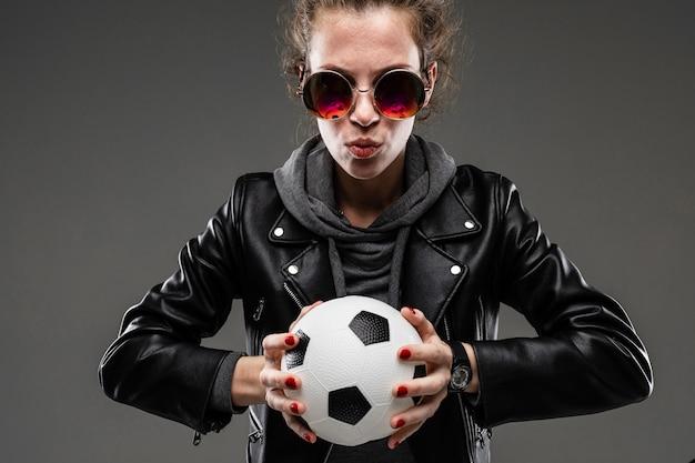 Fille de race blanche avec des traits du visage rugueux dans une veste noire détient un ballon de football isolé sur mur noir