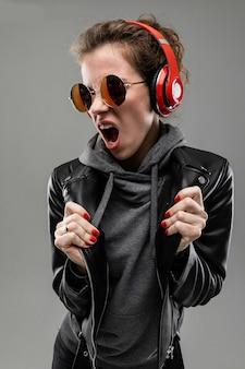 Fille de race blanche avec des traits du visage rugueux dans une veste noire écouter de la musique avec de gros écouteurs isolé sur mur gris