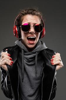Fille de race blanche avec des traits du visage rugueux dans une veste noire écouter de la musique avec de gros écouteurs isolé sur mur noir
