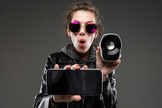Fille de race blanche avec des traits du visage rugueux dans une veste noire écouter de la musique avec téléphone et petite colonne de musique isolé sur mur noir