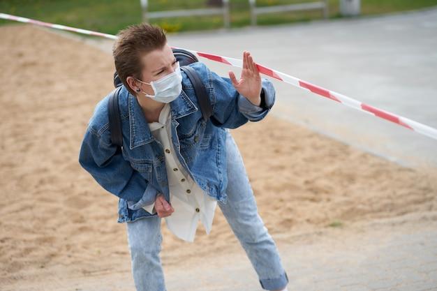 Fille de race blanche traversant la bande de cordon avec un masque médical de protection sur le visage pendant l'épidémie