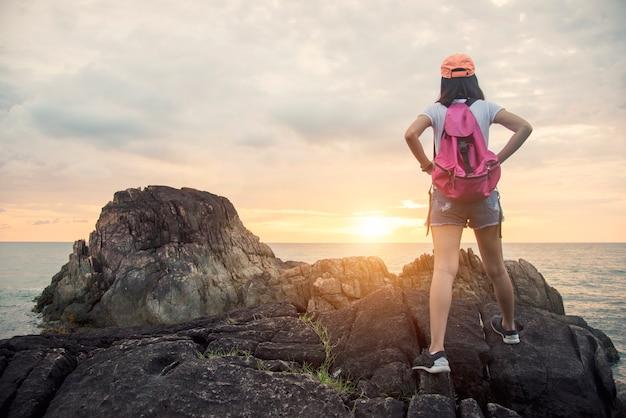 Fille de randonneur randonnée voyage sur la plage de montagne au coucher du soleil