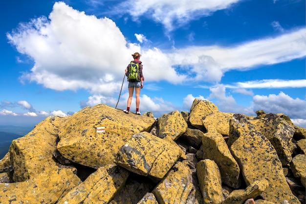 Fille de randonneur tourisme sportif athlétique mince avec bâton et sac à dos escalade éclairée par la haute montagne rocheuse de soleil sur un ciel bleu lumineux.