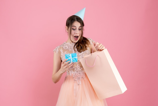 Fille ravie avec chapeau de fête en regardant son cadeau sur rose