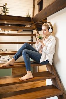 Fille ravie portant des écouteurs tout en écoutant de la musique