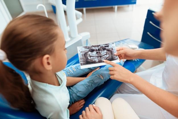 Une fille à la réception d'un dentiste avec ses parents.
