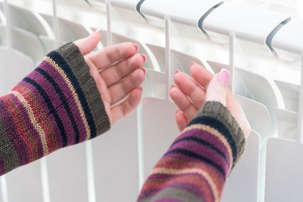 Fille réchauffe les mains gelées au-dessus du radiateur chaud, vue rapprochée