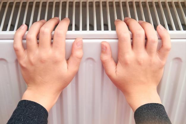 Fille réchauffe ses mains sur le radiateur