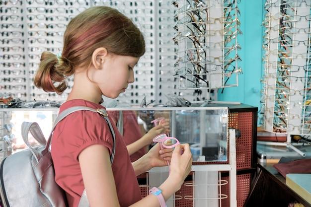 Fille à la recherche et en choisissant des lunettes, enfant près de vitrine en magasin de lunettes