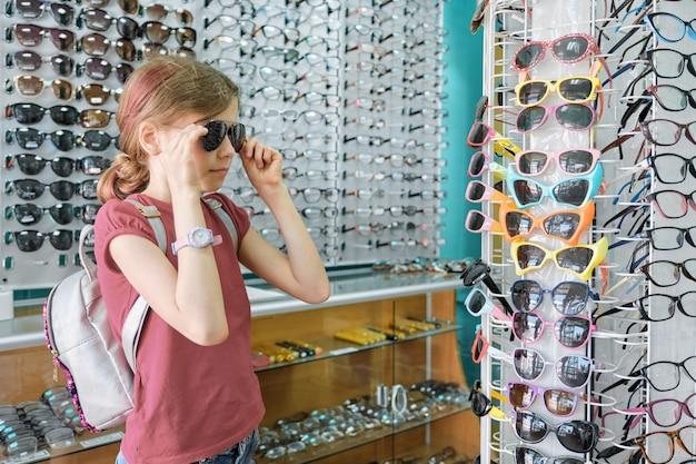 Fille à la recherche et le choix de lunettes de soleil, enfant près de vitrine en magasin de lunettes