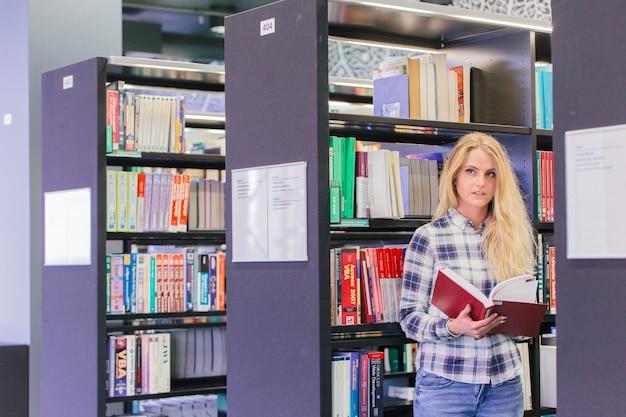 Fille recherche livre dans la bibliothèque
