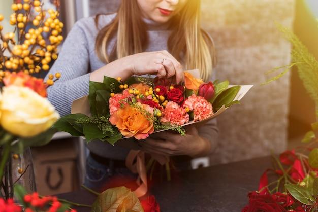 Fille recueille un bouquet de fleurs diverses. petite entreprise