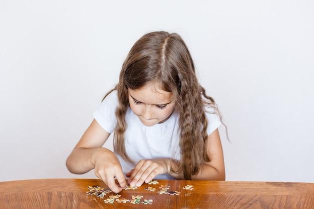 La fille en recueille des morceaux pour faire une image, des puzzles, le développement de l'esprit, les compétences, la compréhension, le jeu, passer du temps, communiquer avec les parents, maman