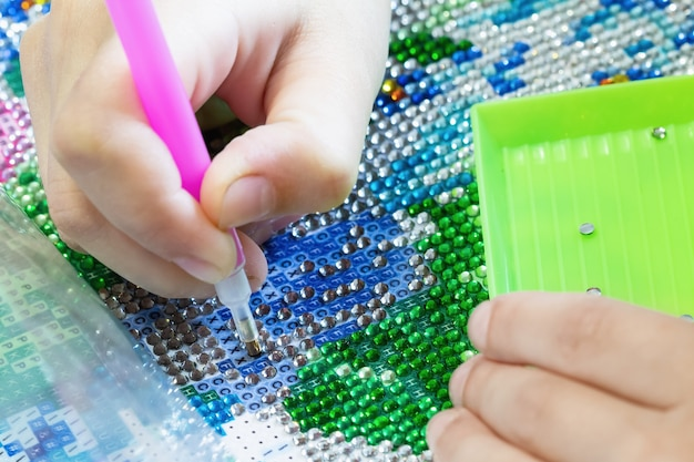 Fille recueillir la peinture au diamant broderie au diamant avec un stylo gros plan mise au point sélective